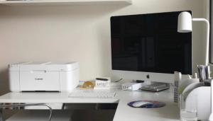 Bel tiskalnik na beli pisalni mizi skupaj z Applovim ekranom.