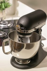 Kuhinjski robot v črni barvi na kuhinjskem pultu.