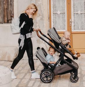 Mamica z vozičkom sprehaja kar dva svoja otroka naenkrat, enega spodaj, enega zgoraj.